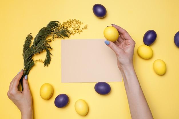 Bella composizione nella regolazione della tavola di pasqua con la cartolina d'auguri in bianco