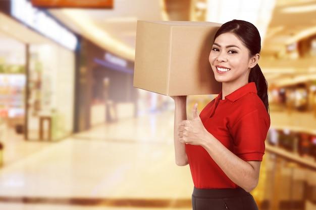Bella consegna femminile asiatica che tiene il pacchetto
