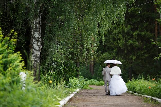 Bella coppia appena sposata sotto l'ombrello