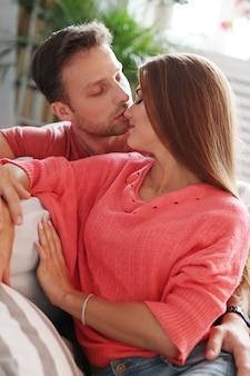 Bella coppia baciarsi nel divano