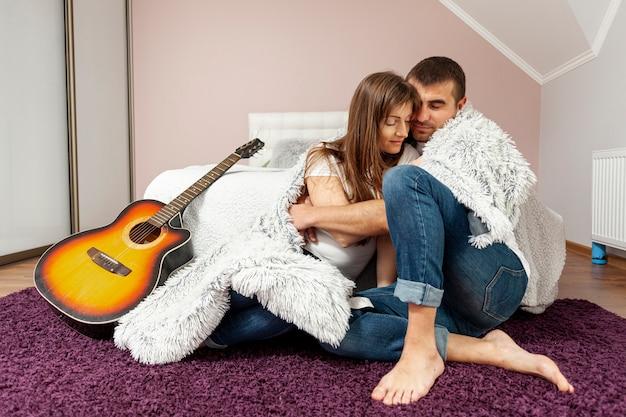Bella coppia che copre con una coperta