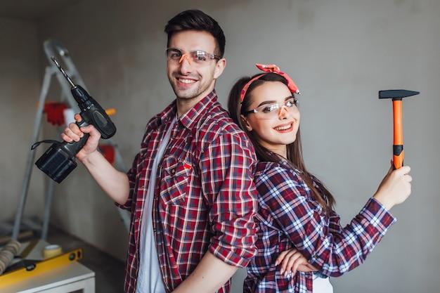 Bella coppia che fa la riparazione a casa, indossando abiti protettivi ben equipaggiati con facce e vestiti disordinati riparazioni a casa