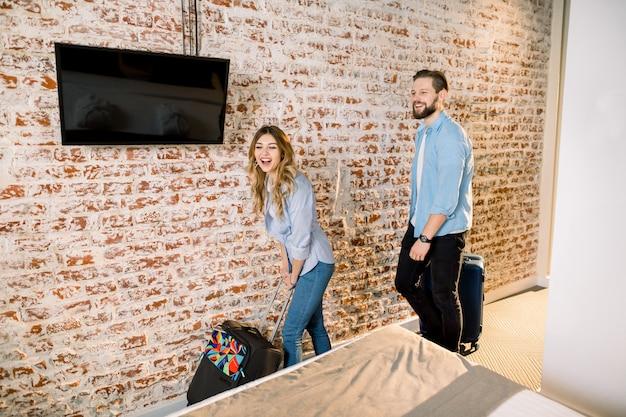 Bella coppia che trascorre un weekend romantico o un viaggio d'affari, aprendo la porta della moderna camera d'albergo
