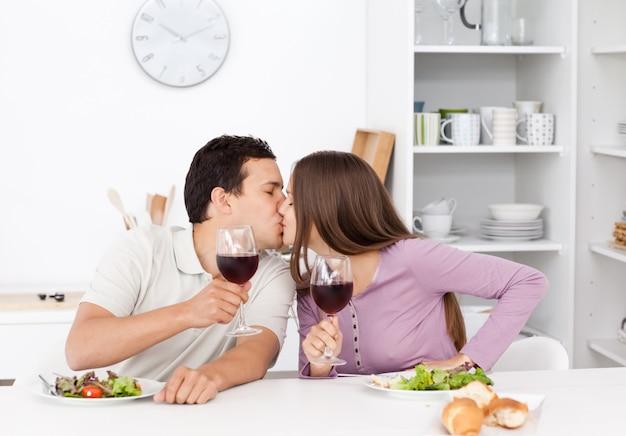 Bella coppia dando un brindisi mentre si mangia un'insalata