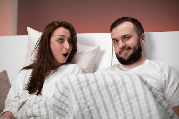 Bella coppia di innamorati si siede nel letto. ragazzo sollevato coperta per ragazza sorpresa