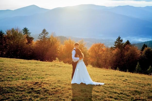 Bella coppia di sposi, innamorati in montagna. lo sposo in un bellissimo abito e la sposa in un abito bianco di lusso. la coppia di sposi sta camminando