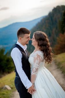 Bella coppia di sposi, innamorati sul muro delle montagne. lo sposo in un bellissimo abito e la sposa in un abito bianco di lusso. la coppia di sposi sta camminando