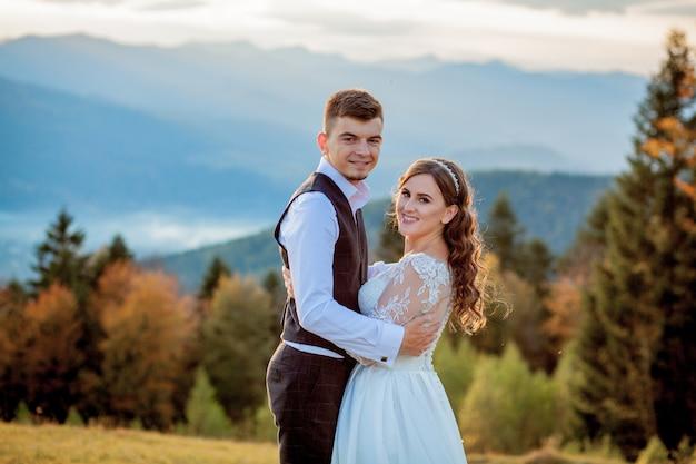 Bella coppia di sposi, innamorati sullo sfondo delle montagne. lo sposo in un bellissimo abito e la sposa in un abito bianco di lusso.