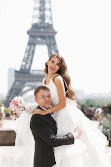 Bella coppia di sposi si diverte a posare sulla piazza prima della torre eiffel a parigi