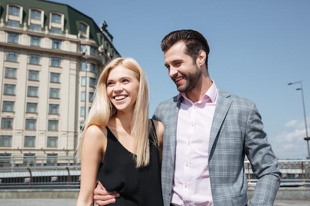 Bella coppia di uomo allegro e donna che cammina in strada