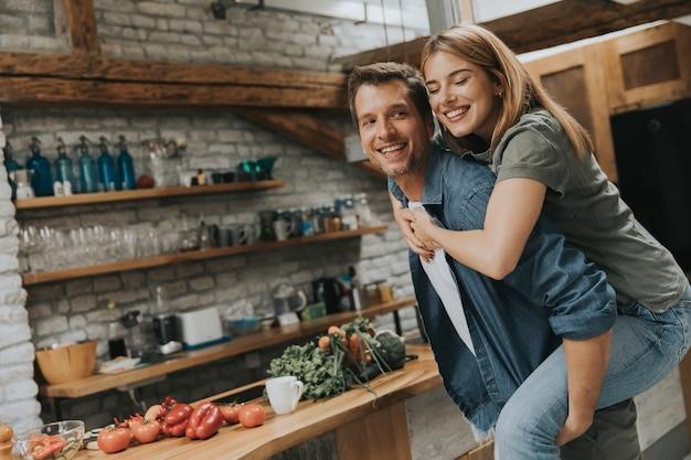 Bella coppia divertirsi insieme alla cucina rustica