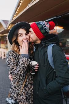 Bella coppia gioiosa agghiacciante, abbracciando sulla strada nel periodo natalizio. vere emozioni d'amore, divertirsi, godersi lo stare insieme, appuntamenti, relazioni romantiche, felicità insieme.