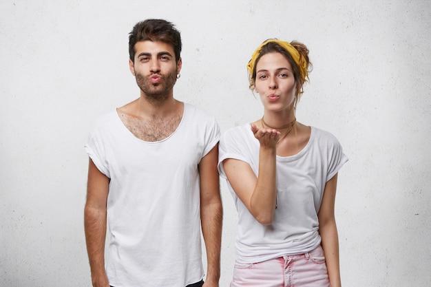 Bella coppia in abiti casual bianchi che soffia bacio mostrando il loro amore.