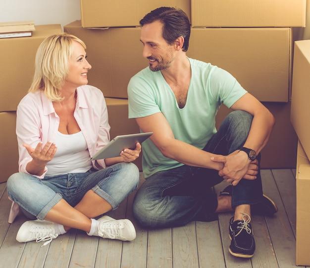 Bella coppia in abiti casual è seduta sul pavimento.