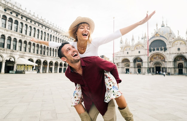 Bella coppia innamorata divertirsi abbracciando e ridendo facendo cavalluccio in vacanza a venezia, italia in piazza san marco.