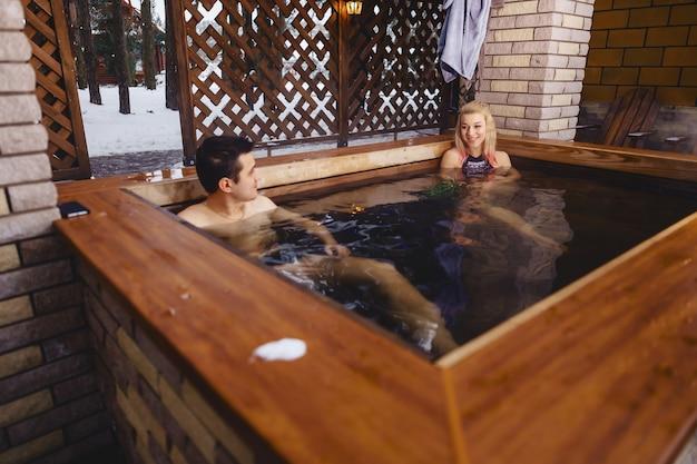 Bella coppia nella vasca idromassaggio in inverno