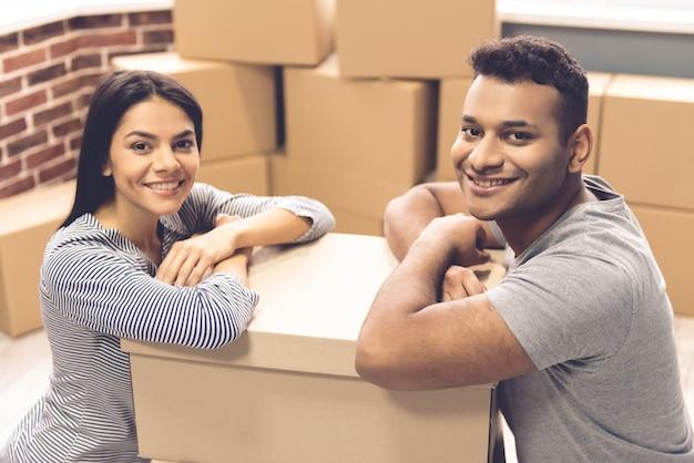 Bella coppia si appoggia sulle scatole in movimento
