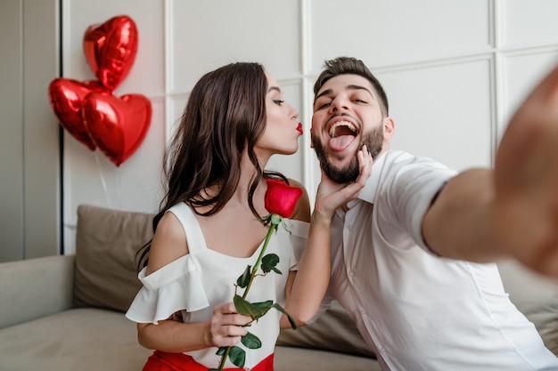 Bella coppia uomo e donna che fanno selfie con rosa rossa e palloncini a forma di cuore a casa sul divano
