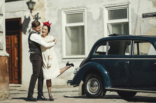 Bella coppia vestita in stile anni '30 abbracci per strada in piedi davanti a una vecchia auto