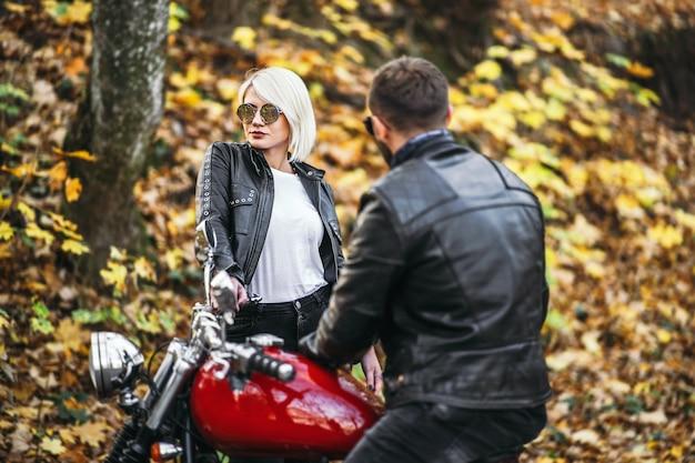 Bella coppia vicino alla moto rossa sulla strada nella foresta