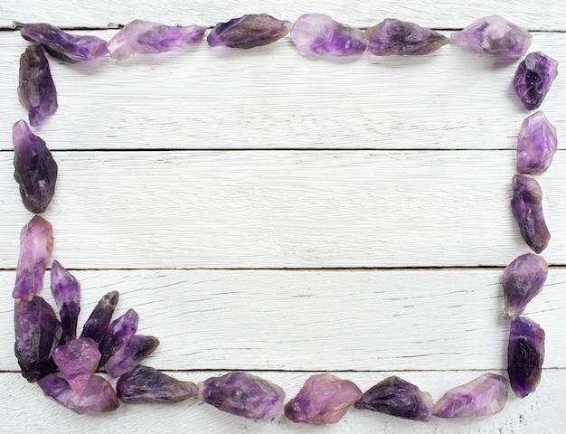 Bella cornice dei denti di cane di quarzo ametista viola cristallo grezzo su fondo in legno