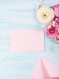 Bella cornice del ranuncolo su fondo in legno turchese. matrimonio per la festa della mamma. holiday elegante mazzo di fiori. carta rosa da riempire con il testo