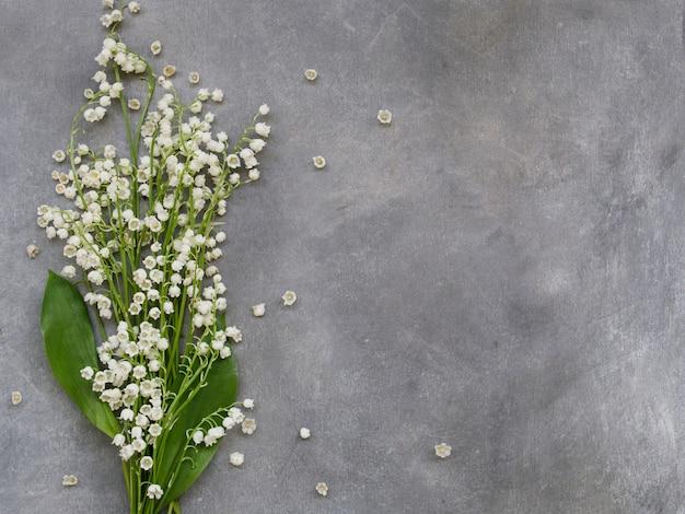 Bella cornice floreale con fiori di gigli della valle su uno sfondo grigio scuro