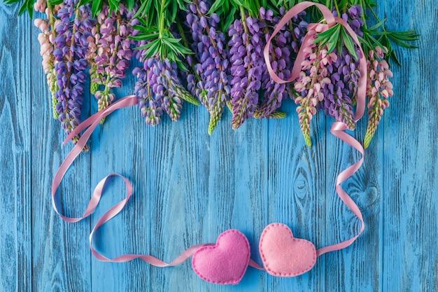 Bella cornice floreale con fiori di lupino sul vecchio tavolo di legno