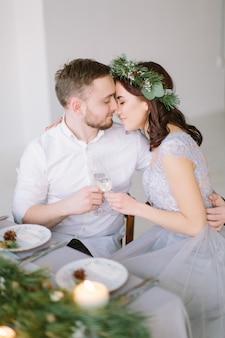 Bella damigella d'onore in ghirlanda di pino e groomman al tavolo di nozze che abbraccia e bacia