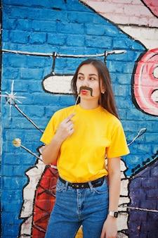 Bella divertente ragazza adolescente con banana a portata di mano, indossare maglietta gialla, jeans e baffi sul bastone vicino al muro di graffiti.