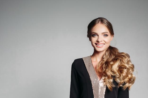 Bella, dolce bionda con i capelli mossi, in un elegante abito di design. amichevole, sorridendo felicemente. guarda la telecamera isolare su uno sfondo grigio.