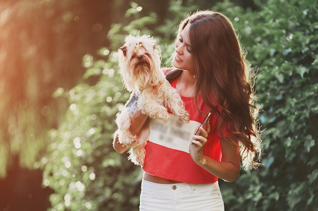 Bella donna a piedi con il cane nel parco.