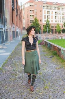 Bella donna adulta che cammina all'aperto guardando lontano premuroso