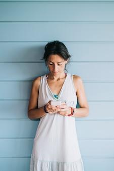 Bella donna adulta che si appoggia su una parete di legno mentre si utilizza uno smartphone