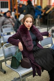Bella donna affascinante con un trucco in un cappotto di borgogna seduto alla stazione
