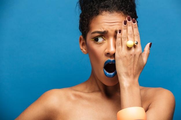 Bella donna afro-americana con il trucco colorato che esprime eccitazione o sorpresa che copre un occhio con la mano, isolato su muro blu