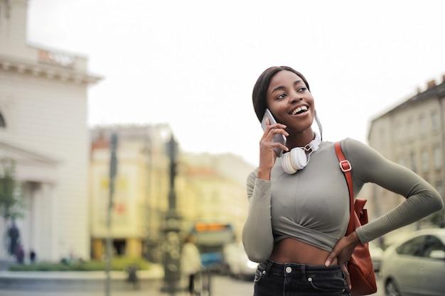 Bella donna afro parlando su uno smartphone