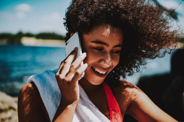 Bella donna afroamericana che parla sul telefono.