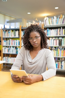 Bella donna afroamericana che posa alla biblioteca