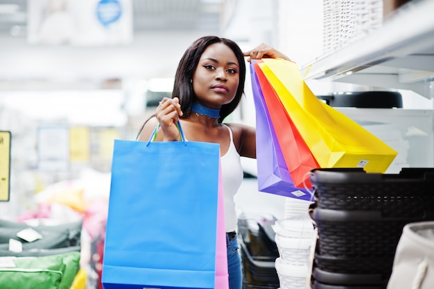 Bella donna afroamericana che tiene i sacchetti della spesa multicolori in un deposito.