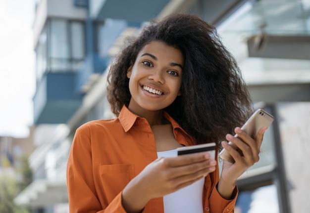 Bella donna afroamericana sorridente che compera online, tenendo la carta di credito