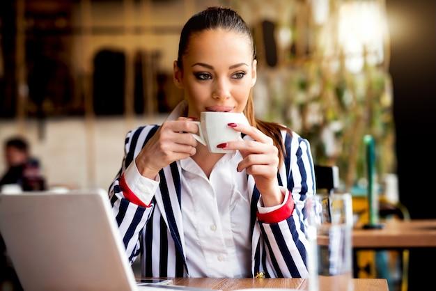 Bella donna al bar caffetteria bere caffè.