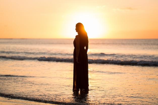 Bella donna al tramonto. alba colorata sul mare. donna spensierata che gode del tramonto sulla spiaggia. stile di vita felice