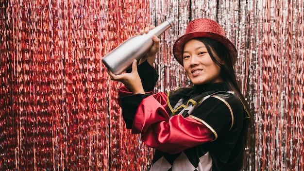 Bella donna alla festa di carnevale con bottiglia di champagne