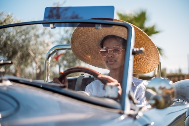 Bella donna alla guida di un'auto convertibile vintage