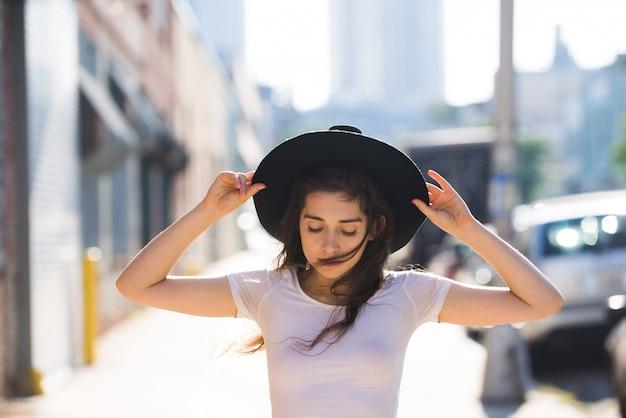 Bella donna alla moda dell'adolescente che posa con il cappello