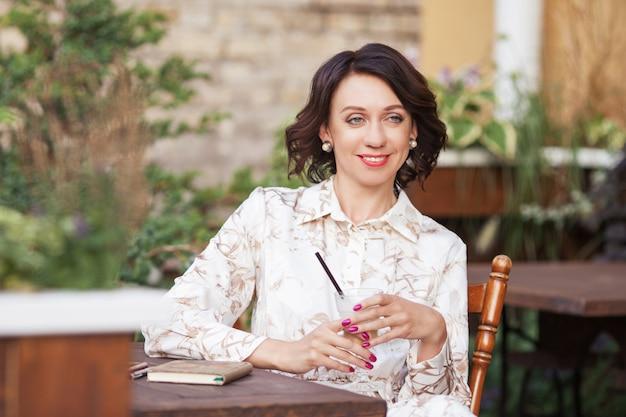 Bella donna alla moda in vestito beige che beve caffè all'aperto presso la caffetteria. ritratto di donna felice nella caffetteria all'aperto