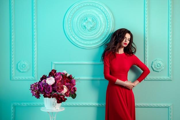 Bella donna alla moda sexy vicino alla parete decorata verde. mazzo di fiori. vestito rosso.