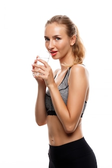 Bella donna allegra che posa, tenendo bicchiere d'acqua