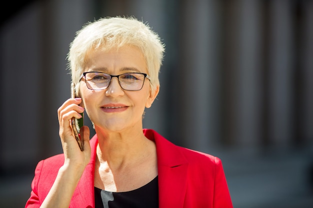 Bella donna anziana in età con un taglio di capelli corto e occhiali in una giacca rossa con un telefono